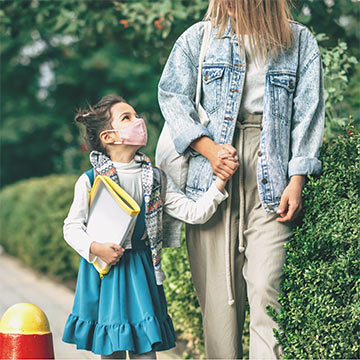 young child with caregiver on their way back to school