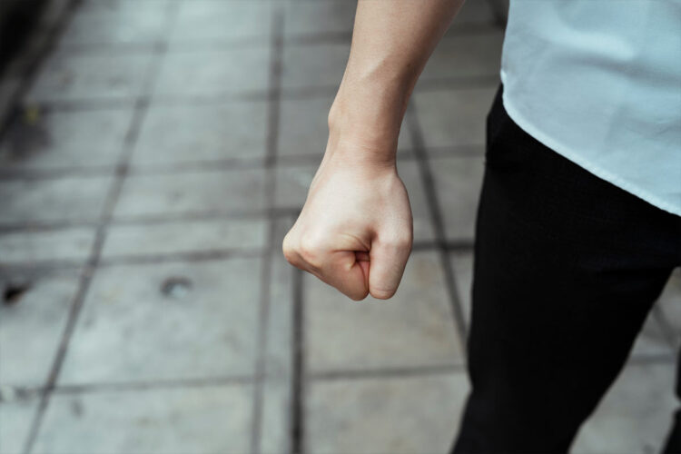 young person's clenched fist held at side