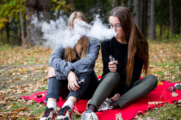 two young people vaping near woods