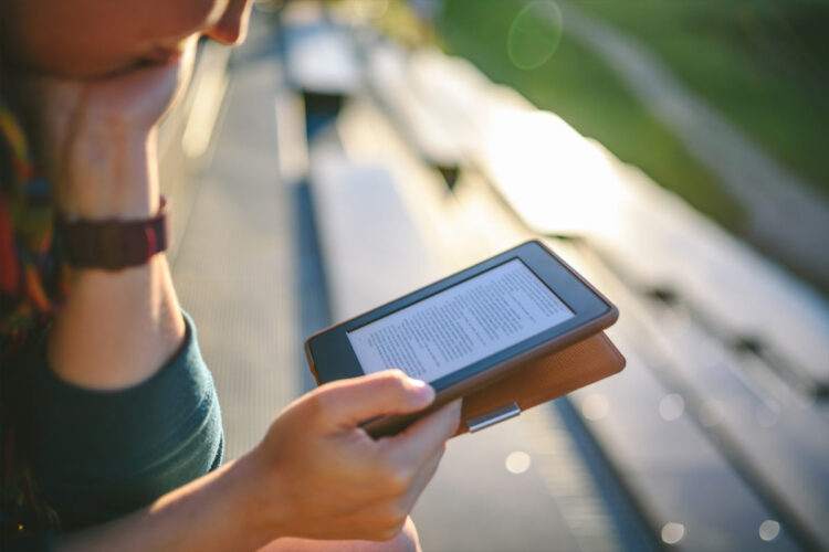 young person reading on an e-reader on bleachers