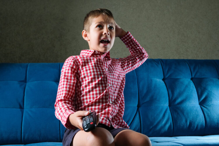 excited child on couch with tv remote