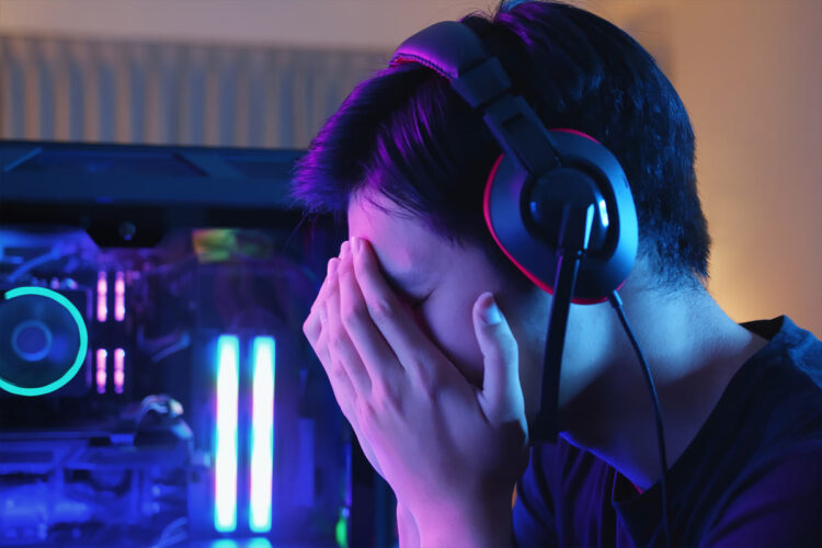 child with head in hands next to gaming computer