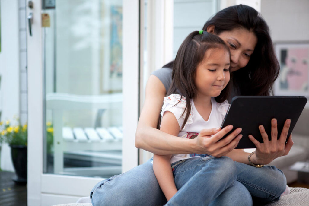adult with child in lap looking at tablet