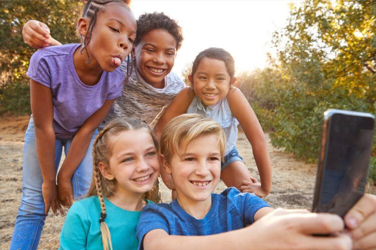 five children taking group selfie outside