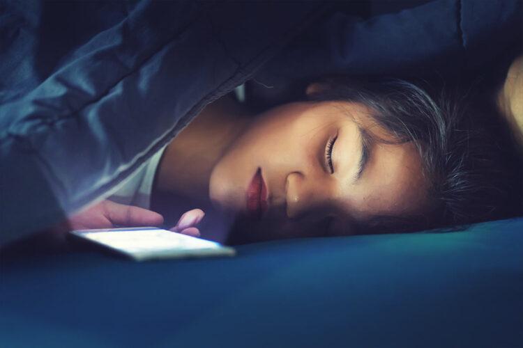 child asleep next to bright phone screen