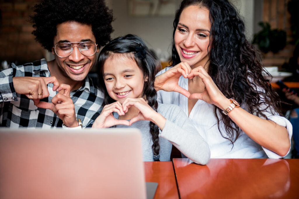 family of three making hearts with hands toward webcam