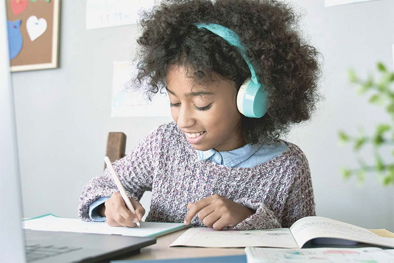 child doing schoolwork with headphones and laptop