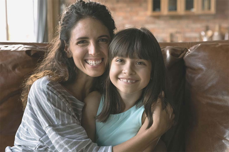 child with parent smiling for camera