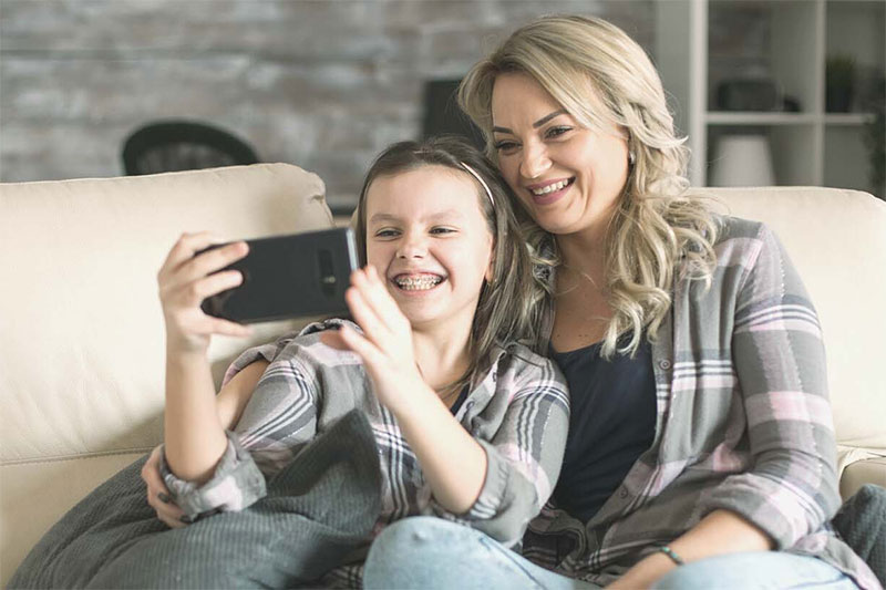 child with parent watching phone