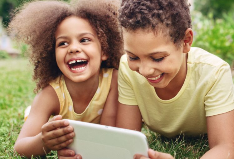 two youths happy with tablet on lawn