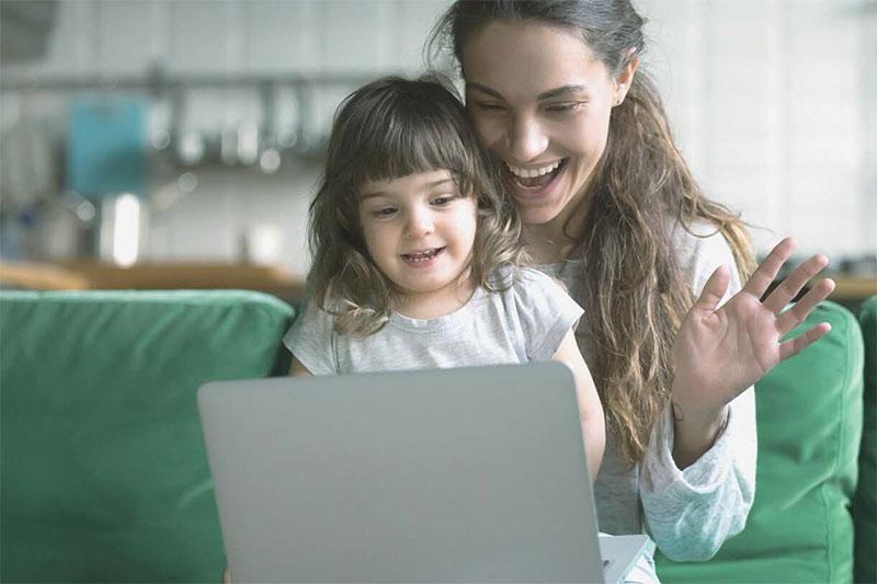 preschooler with parent smiling at laptop