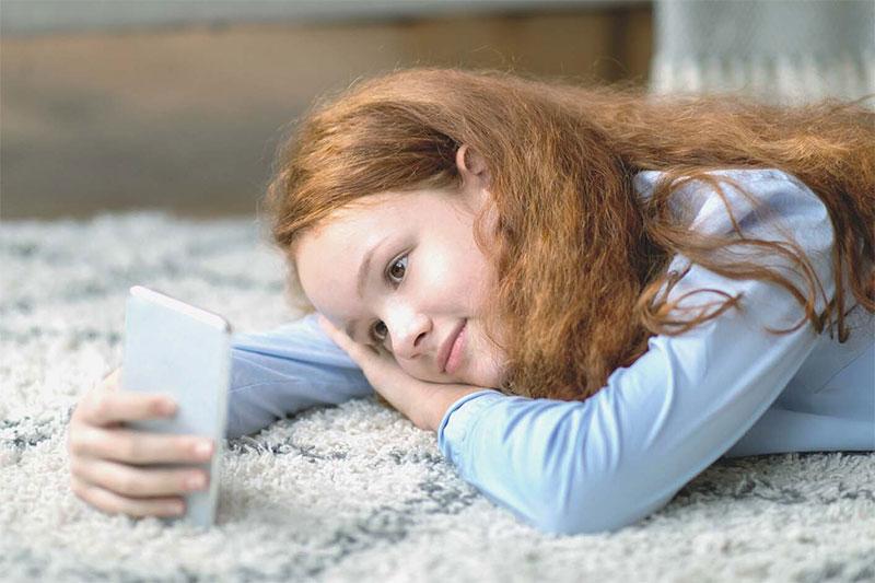 tween on carpet with phone