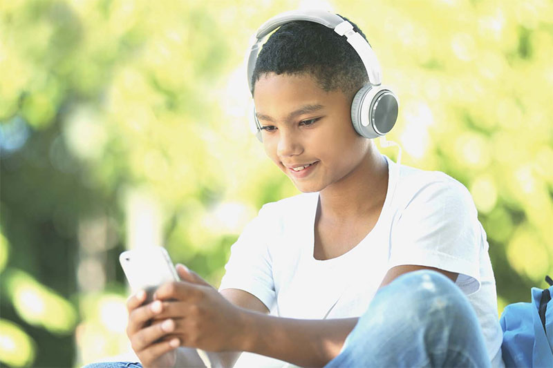 tween with headphones and phone outside