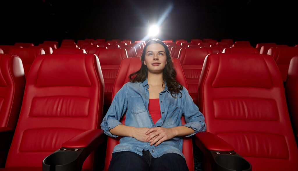 Young woman in an empty movie theater